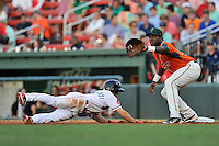 Center fielder Andrew Benintendi (2) of the Greenville Drive dives back to first with K.J Woofs of the Greensboro Grasshoppers defending on Thursday, August 27, 2015, at Fluor Field at the West End in Greenville, South Carolina. Benintendi is a first-round pick of the Boston Red Sox in the 2015 First-Year Player Draft out of the University of Arkansas. Greenville won, 10-2. (Tom Priddy/Four Seam Images)