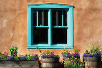 Potted flowers display and colorful window of adobe house along Canyon Road. Santa Fe, New Mexico