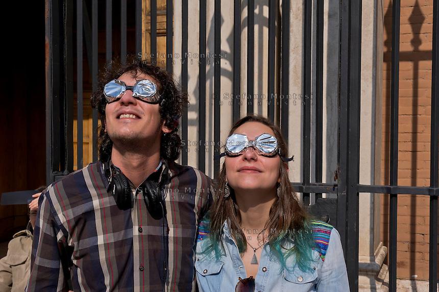 Roma 20 Marzo 2015<br /> Eclissi solare parziale al quartiere San Lorenzo. La gente si riunita questa mattina in Piazza Immacolata, per osservare  l'eclissi solare parziale.  Due giovani guardano  l'eclissi solare parziale, attraverso occhiali auto-prodotti.<br /> Rome March 20, 2015<br /> Partial solar eclipse. People gather this morning in Piazza Immacolata, District San Lorenzo, to get a rare glimpse of the solar eclipse. Two young watch the partial solar eclipse, through with the self-produced glasses