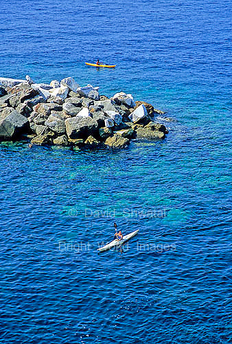 Two kayakers round a breaker in the Mediterranean sea near Riomaggorie, in the Cinque Terre, Italy.