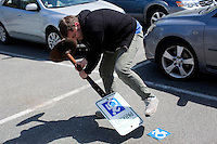 Dr. Brian Glenney, Professor of Philosophy at Gordon College, in Wenham, Massachusetts, applies a sticker with the Accessible Icon to a parking sign at Gordon College.  Glenney helped develop the Accessible Icon as part of the Accessible Icon Project.  The icon is a redesign of the International Symbol of Access (also known as the handicap symbol) that shows an active and engaged person with arms in motion.  Glenney's research focuses on the philosophy of perception and he maintains active interest in graffiti and street art.  The Accessible Icon has been adopted by cities and institutions around the world, including Gordon College, Nissan, New York City, Malden, MA, and others.