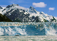 Tour boat Discovery dwarfed by Meares tidewater glacier, Meares inlet, Prince William Sound, Alaska.