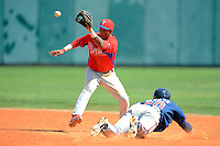 Philadelphia Phillies infielder Angelo Mora (28) takes a throw as Jose Peraza (30) slides in during a minor league Spring Training game against the Atlanta Braves at Al Lang Field on March 14, 2013 in St. Petersburg, Florida.  (Mike Janes/Four Seam Images)