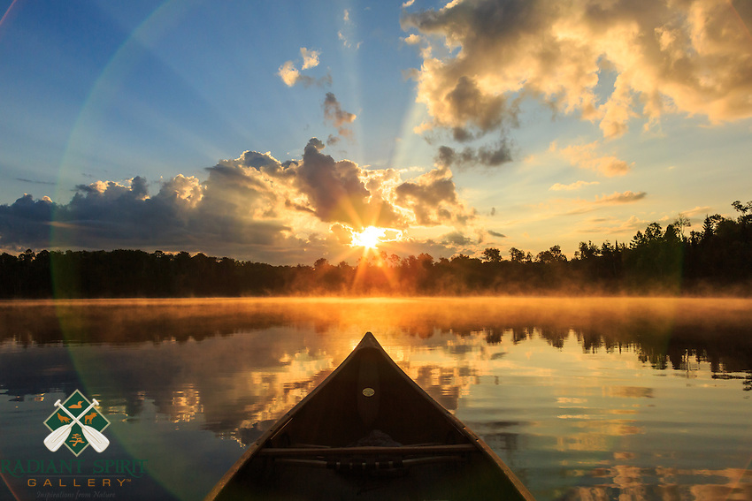 &quot;Canoe Country Radiance I&quot;<br /> <br /> A tranquil sunrise streaming through the clouds as viewed from my canoe gives rise to corpuscular rays, camera lens flare, and illuminated fog making this one of my favorite shots. Basswood Lake, Pipestone Bay in the BWCAW.