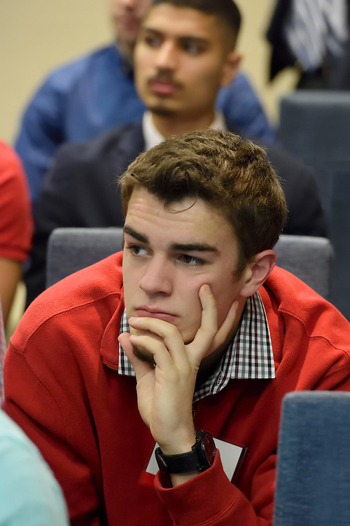 Candid closeup of a student listening to a speaker at a seminar.