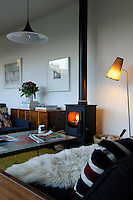 A contemporary living room that sees Scandinavian Modern style in a homely, contemporary space. A free-standing log burner adds a warm glow to the room.