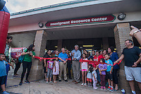 NWA Democrat-Gazette/ANTHONY REYES &bull; @NWATONYR<br /> Springdale mayor Doug Sprouse cuts a ribbon Tuesday, Aug. 18, 2015 at the block party and ribbon cutting for the Immigrant Resource Center in Springdale. The Center is the first of five planned for the state. It is a cooperation between Arkansas United Community Coalition and Catholic Charities Immigration Services of Northwest Arkansas and will provide area immigrants with immigration navigation services, leadership development opportunities, and civic integration support. The event introduced the public to the services provided by the center and several other organizations were on hand to distribute information about their organizations.