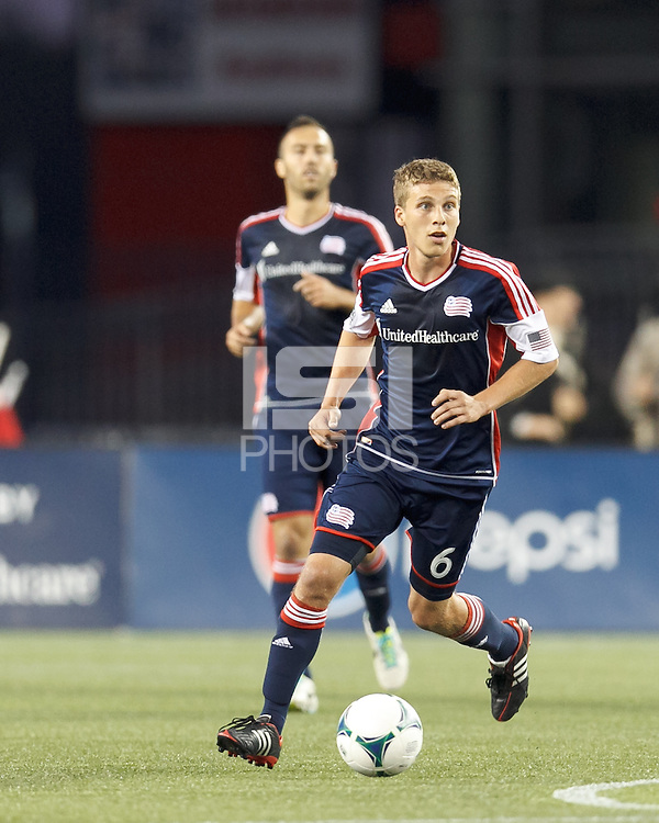 New England Revolution midfielder Scott Caldwell (6) brings the ball forward.  In a Major League Soccer (MLS) match, the New England Revolution (blue) defeated Chicago Fire (red), 2-0, at Gillette Stadium on August 17, 2013.