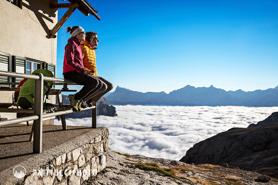 Couple relaxing in the morning sun at the Rifugio Pisciadú before starting on day 2 of the Dolomites Alta Via 2