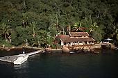 Ilha Grande, Brazil. Luxury modern holiday house built close to the sea with veranda and hammocks, motor boat.