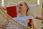 Mid adult man reading book, lying down in hammock