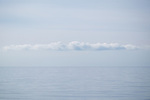 Calm seascape with clouds in blue sky