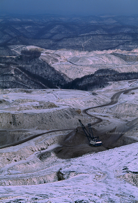 Big John, a dragline, sits idle on a mountaintop removal mine. Draglines are amongst the largest mobile equipment ever built on land, and weigh in the vicinity of 2000 metric tonnes, though specimens weighing up to 13,000 metric tonnes have also been constructed.<br /> A dragline bucket system consists of a large bucket which is suspended from a boom (a large truss-like structure) with wire ropes. The bucket is manoeuvred by means of a number of ropes and chains.