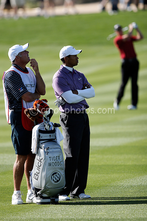 Feb 23, 2008; Marana, AZ, USA; Tiger Woods and caddie Steve Williams stand in the fairway while Henrik Stenson hits his approach shot into the 18th green of their semifinal match at the Accenture Match Play Championship at the Gallery Golf Club.