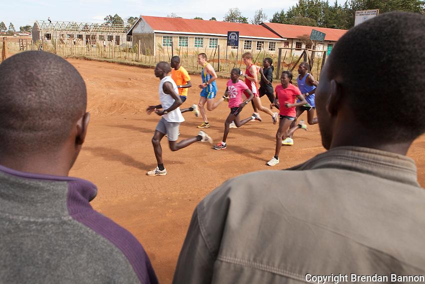 A group of elite atheletes including Kenyan Florence Kiplagat and belgian marathoners begin a training run as people waiting for a bus watch in Kaplelach, Kenya.