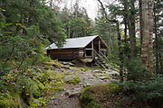 The Log Cabin in the White Mountains of New Hampshire. This shelter is located along Lowes Path at 3,263 feet in the Northern Presidential Range. It is designed after the Alaskan trapper style building and is located in a Forest Protection Area.