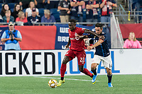 FOXBOROUGH, MA - AUGUST 31: Richie Laryea #22 of Toronto FC brings the ball forward as Diego Fagundez #14 of New England Revolution pressures during a game between Toronto FC and New England Revolution at Gillette Stadium on August 31, 2019 in Foxborough, Massachusetts.