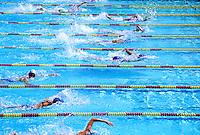 Teens in swimming pool race .