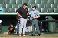 Delmarva Shorebirds manager Ryan Minor (44) has a discussion with home plate umpire Sam Burch between innings of the South Atlantic League game against the Kannapolis Intimidators at Kannapolis Intimidators Stadium on July 2, 2017 in Kannapolis, North Carolina.  The Shorebirds defeated the Intimidators 5-4.  (Brian Westerholt/Four Seam Images)