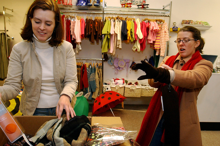 Owner of Plaid, Sarah Chellgren, left, sorts through new inventory while Andrea Roy Chernack, tries on gloves in Chellgren's store on 8th Street, SE.