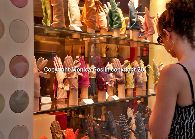 A woman admired leather gloves and Italian leather goods in a shop window in Venice, Italy