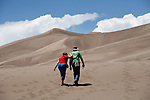 An elderly couple hikes through Great Sand Dunes National Park, the tallest dunes in North America, at the edge of the Sangre de Christo Mountains in Southern Colorado.