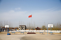 A Chinese flag flies above basketball hoops in the schoolyard at Yixing Middle School in Lianshui County, Jiangsu Province, China.  The Pfrang Association, a German charity based in Nanjing, China, sponsors a number of children in the school, providing money for boarding, food, clothing, school supplies, and other necessities to continue schooling.  The majority of children at this school come from poor farming families in rural Jiangsu Province, China.
