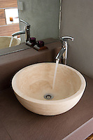In the bathroom water gushes from a stainless steel tap designed in a pared-down minimalist style into a simple round travertine basin