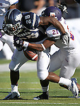 Northwestern State's Brashard Booker (21) causes Nevada's Stefphon Jefferson (25) to fumble the ball during the first half of an NCAA college football game Saturday, Sept. 15, 2012, in Reno, Nev. (AP Photo/Cathleen Allison)