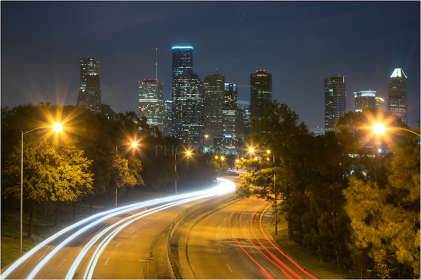 rom a Pedestrian bridge that spans both Buffalo Bayou and Memorial Parkway, this is the view you can enjoy in the evening as traffics flows to and from the beautiful Houston Skyline. This image of downtown was captured using a long exposure to allow the headlights and taillights to flow up and down the busy street. In the distance the high rises from the largest city in Texas rise into the night sky. This image  is available both as a fine art print and for licensure as a digital file.