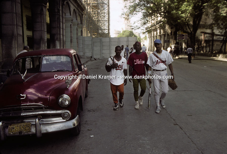 A 1956 Dodge parked on a Havana street as three men dressed in baseball unforms walk by in 1998.