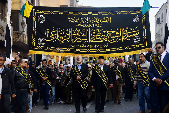 """Egyptian Sufi Muslims chant prayers while walking in a march with banners as they celebrate """"Mawlid al-Nabawi"""" or the birth of Prophet Mohammad, in old Cairo, Egypt, on December 11, 2016. Photo by Amr Sayed"""