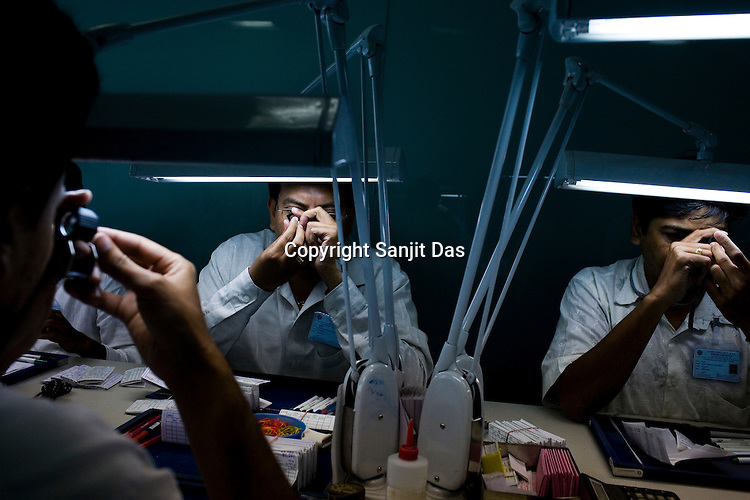 Diamond specialists check the shapes of the rough diamonds in the planning section at the diamond cutting and polishing factory in Surat, Gujarat, Western India.