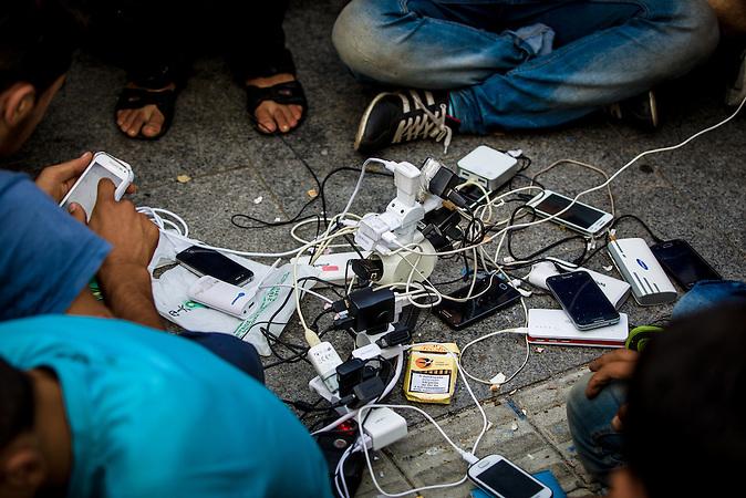 Flüchtlinge laden ihre Mobiltelefone an den Steckdosen der internationalen Presse auf.