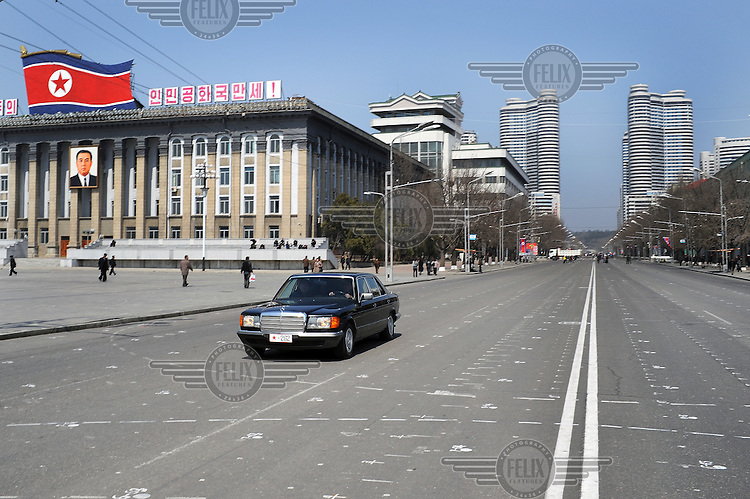 A Mercedes limousine, the on vehicle on a road that passes Kim Il-sung Square. In the background are the newly built buildings of  Mansudae Street, finished just on time for celebrations marking the 100th birthday of Kim Il-sung.