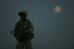 A Marine from Kilo Co. 3rd BN 1st Marines walks through the desert by moonlight during a night patrol on the outskirts of Fallujah in the last days before the Nov. 2004 assault on the city.