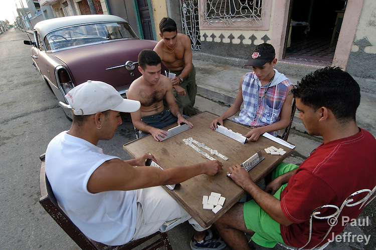 Youth playing dominos on the street in Cardenas, with an old car - a trademark of life in Cuba - in the background.