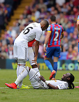 Pictured L-R: Kenji Gorre of Swansea helps team mate Marvin Emnes with his cramp<br />
