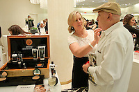 Woman applies Menaji skincare product on man at The Plaza Hotel's Fashion's Night Out event during New York Fashion Week, September 8, 2011.