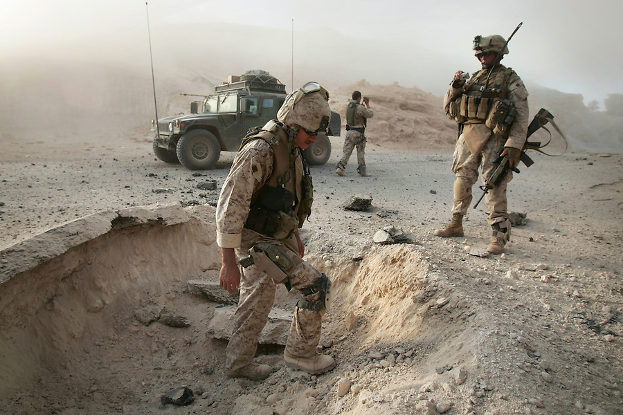 A Marine explosive ordinance disposal team attached to 3rd Battalion 1st Marines (3/1) investigates a crater after utilizing a remote-controlled robot and high explosives to investigate, and destroy an IED discovered by a sweeping infantry foot patrol during  Operation River Gate - the search for insurgents and weapons in the Al-Anbar Province cities of Haditha, Haqlaniya, and Barwanah on Monday, Oct. 10 2005. Such sweeps have discovered dozens of IEDs since the operation commenced a week ago.