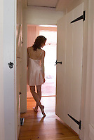 Woman wearing negligee standing in hallway