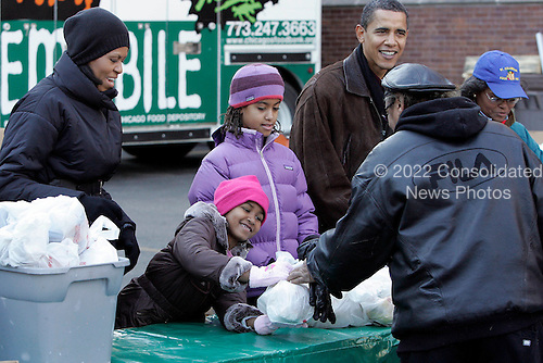 Chicago, IL - November 26, 2008 -- United States President-elect Barack Obama, right, and his wife Michelle, left, Sasha (2nd L) and Malia, pass out food at St. Columbanus Parrish and School Wednesday, November 26, 2008, in Chicago, Illinois. .Credit: Frank Polich - Pool via CNP