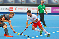 Adam Dixon of England dribbles past Mirco Pruijser of Netherlands during the Hockey World League Semi-Final match between England and Netherlands at the Olympic Park, London, England on 24 June 2017. Photo by Steve McCarthy.