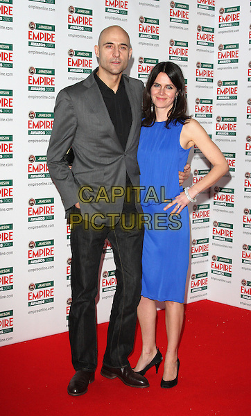 MARK STRONG & GUEST.The Jameson Empire Film Awards, Grosvenor House Hotel, Park Lane, London, England..March 28th 2010.full length black jeans denim grey gray jacket blue dress hand in pocket.CAP/ROS.©Steve Ross/Capital Pictures..