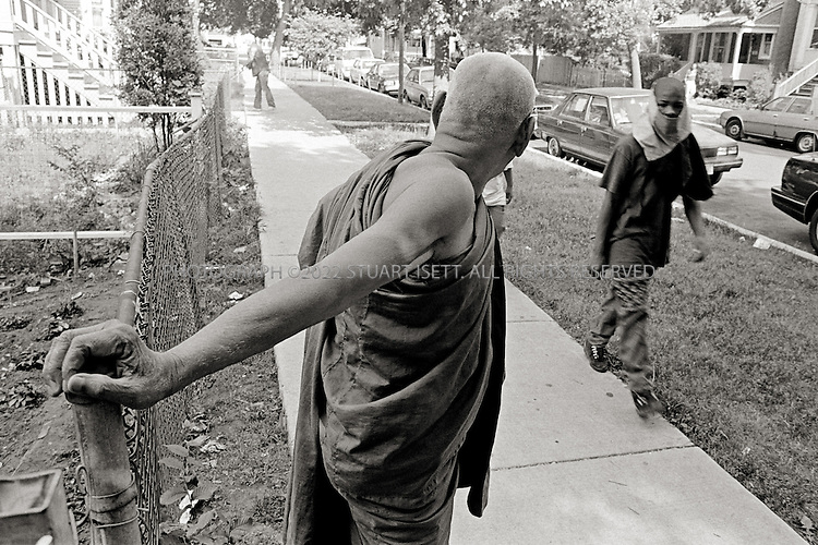 8/1993--Chicago, USA..Phra Khem, the head monk at Wat  Khemararan, holds onto the front fence of the temple while a young black gang member from a nearby public housing complex walks past. Uptown in the 1980s was a gang infested neighborhood, filled with black and Latino gangs as well as white neo-Nazi groups. It was into this neighborhood that thousands of Cambodian refugees, many poor illiterate farmers, were placed and forced to survive. It wasn't long before Cambodian youth started to form gangs, to protect their neighborhood...All photographs ©2007 Stuart Isett.All rights reserved.This image may not be reproduced without expressed written permission from Stuart Isett.