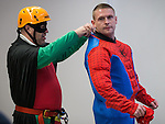 © Joel Goodman - 07973 332324 . 7 December 2013 . Robin helps Spiderman with his kit . In scenes reminiscent of a Fathers for Justice demonstration , people in superhero and Christmas-themed costumes , abseil 107 metres down the New York Street side of City Tower to raise money for the Factory Youth Zone in Harpurhey . Photo credit : Joel Goodman