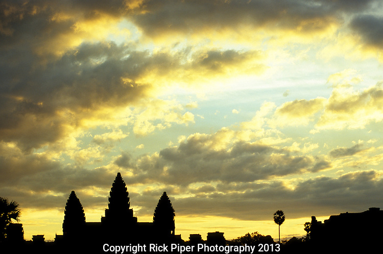Angkor Wat Sunrise 03 - Angkor Wat silhouetted against a yellow cloudy sky at sunrise, from the causeway, Cambodia
