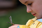 Young girl ( 11 years old) with dragon fly on her hand Lake Mason Olympic Penninsula Washington State USA
