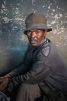 Africa, Madagascar, Ambatolampy village. Man working in aluminum foundry. Maybe one of the most dangerous jobs in Madagascar.