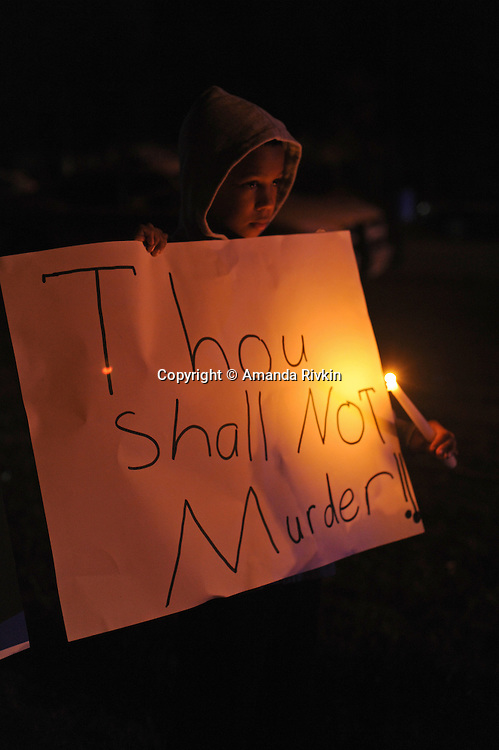 """Desmond Lane, 11, from Richmond, Virginia stands with a poster showing his  disapproval of the death penalty, near the entrance to the Greensville Correctional Center hours before the 9 p.m. execution of John Allen Muhammad, the so-called """"Washington sniper"""" responsible for gunning down 10 and wounding three in the D.C.-area in 2002, in Jarratt, Virginia on November 10, 2009.  Virginia Governor Tim Kaine refused to grant a stay of clemency and the U.S. Supreme Court turned down the request for a stay of execution despite religious objections due to Muhammad's mental health."""